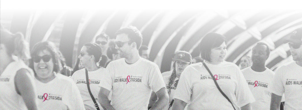 A group of people walking towards the camera. The photo is black and white, with the red logo on the people's t-shirts highlighted as the only colour.